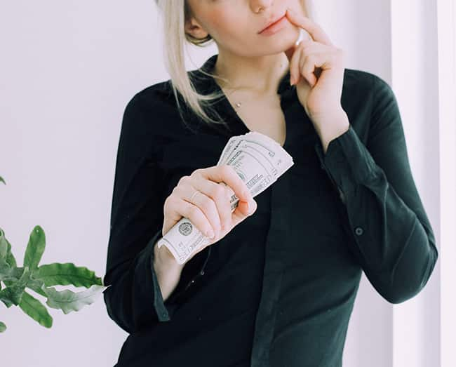Woman holding money and thinking about investments.